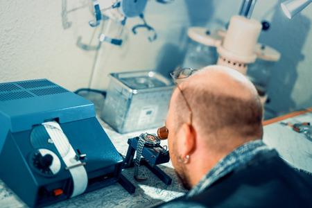 Close-up portret van een horlogemaker bij work.A horlogemaker of reparatie man in actie, het bekijken van zeer nabij een Zwitsers horloge. Stockfoto - 71296861