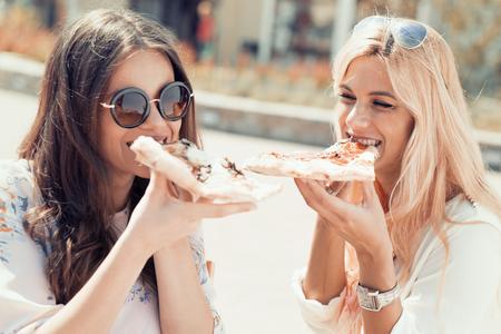 有朋友一個偉大的時間在戶外,吃比薩餅。 版權商用圖片