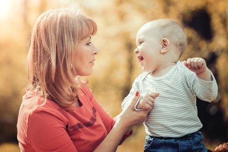 快樂的母親與她在公園夏天的小兒子。