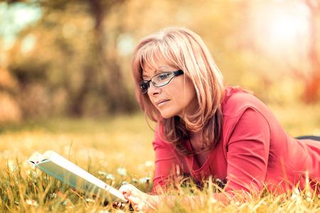 美しい女性は、自然の中の本を読んでの肖像画。