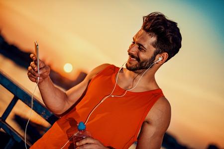 Jeune homme écouter de la musique sur un phone.He smart est à l'écoute de la musique sur téléphone intelligent dans la ville. Banque d'images - 71296846