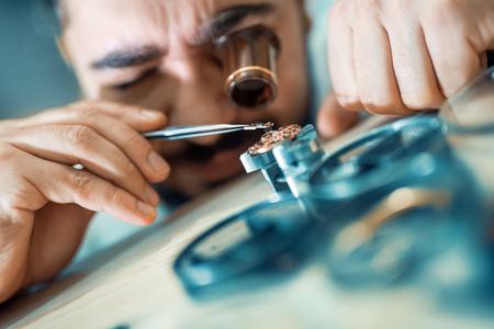 Close-up portret van een horlogemaker bij work.A horlogemaker of reparatie man in actie, het bekijken van zeer nabij een Zwitsers horloge. Stockfoto - 71325476