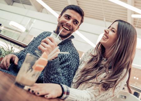 カフェでロマンチックな日付の陽気な若いカップル。