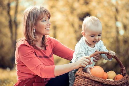 秋の公園で家族。秋の自然の中の息子の子供と遊ぶママ。