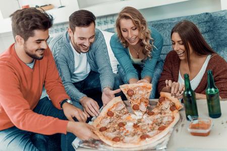 Amis de manger pizza.They ont de fête à la maison, manger de la pizza et avoir du plaisir.