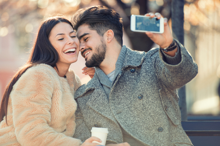Jeune couple de prendre une selfie et avoir du plaisir en plein air.