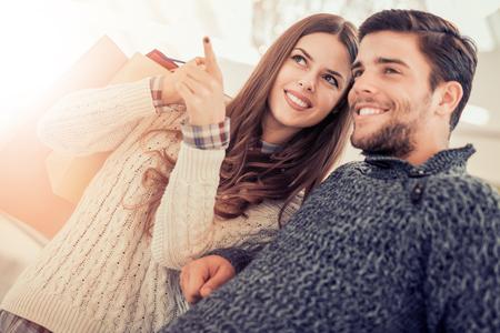 年輕漂亮的恩愛夫妻攜帶購物袋,並一起享受。 版權商用圖片