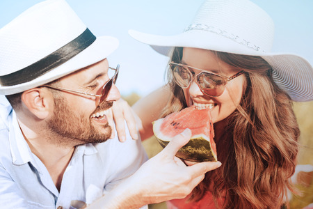 晴れた日にスイカを食べてピクニックに幸せなカップル。