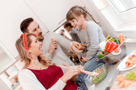 Happy young family preparing lunch in the kitchen and enjoying together.