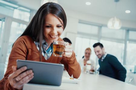 若い女性がカフェでカップからお茶を飲みます。