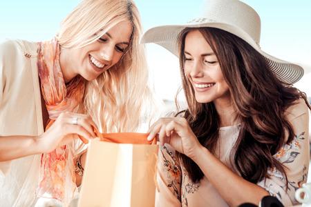 Dos mujeres jóvenes que relajan en café después de las compras.