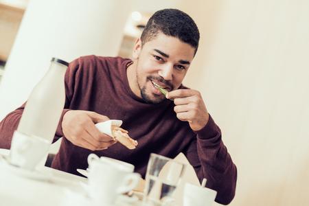 レストランのバーで食べることの若いハンサムな男。