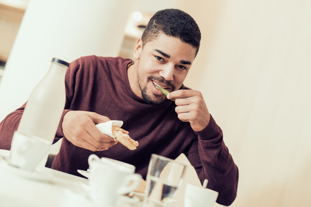 Jeune homme beau manger dans un bar-restaurant. Banque d'images - 71299549