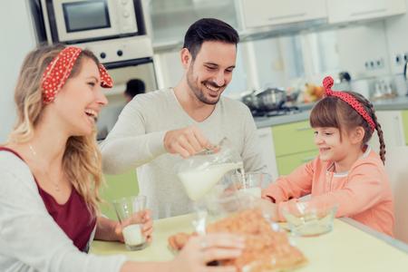 Familia que come el desayuno juntos en la cocina.