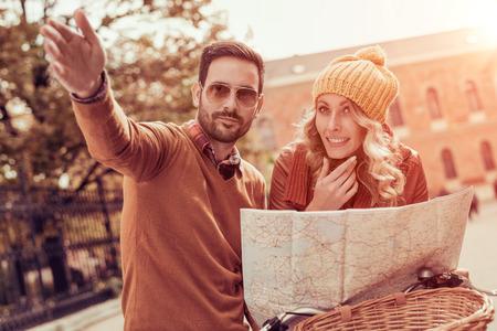 観光客のカップル。若いカップルが町の場所の町の地図を使用して.