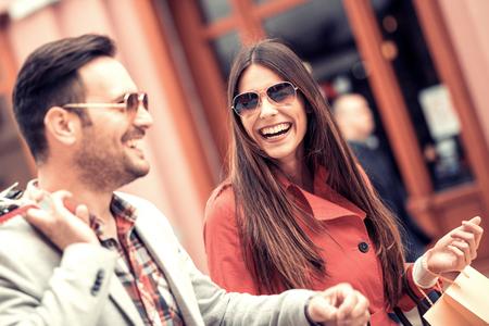 若いカップルが買い物袋を保持しています。販売、消費、人々 の概念。