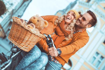 街での楽しみを持っている若いカップル。自転車のために行く幸せな若いカップルは、街で乗る。