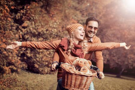 Jeune couple ayant du plaisir dans le jeune couple park.Happy aller pour une balade à vélo sur une journée d'automne dans le parc.