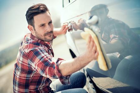 若い男が彼の車を屋外の洗浄します。男は車磨きマイクロファイバーで拭きます。