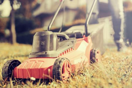 男子割草在他的院子裡用割草機。