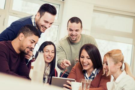 Prise de vue d'un des amis ayant un bon moment à cafe.Friends souriant et assis dans un café, boire du café et profiter ensemble. Banque d'images - 71325528