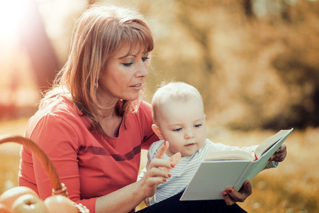 Picture of mature woman with son sitting down on green grass field and read fairytale in park. Stock Photo