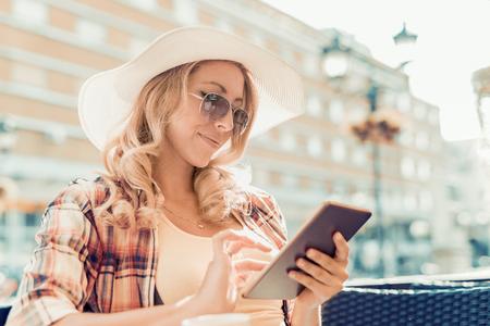 Mujer hermosa en la ciudad que usa la tableta digital. Foto de archivo