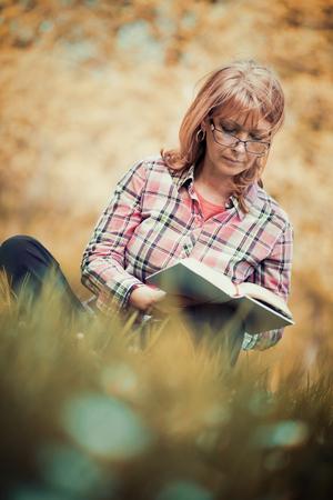 Portrait de femme beau livre de lecture dans la nature.