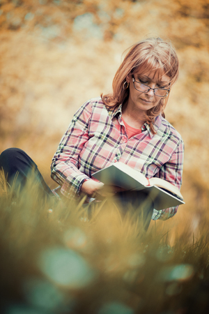 Portret van mooie vrouw leesboek in de natuur. Stockfoto - 71299912