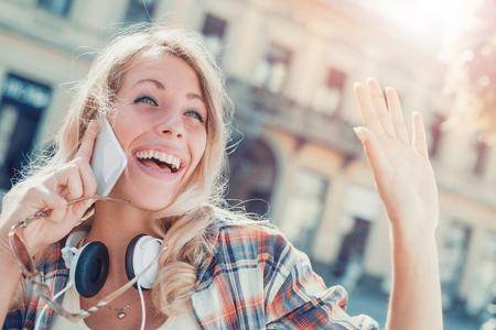 Mujer joven que escucha la música en un teléfono inteligente en la ciudad. Foto de archivo