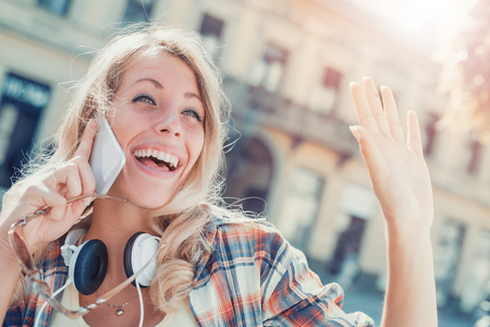 Young woman listening to music on a smart phone in the city. Stock Photo