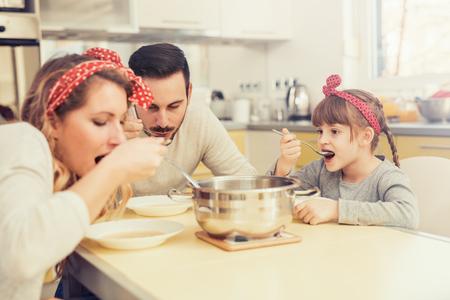 Jeune famille dans la cuisine manger le déjeuner à la table de cuisine. Banque d'images