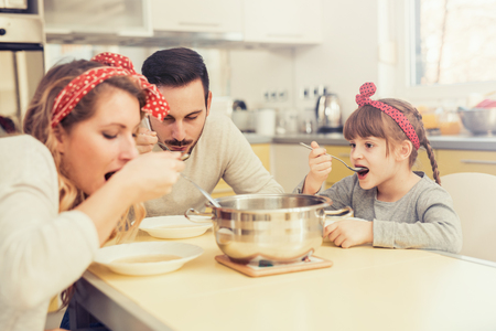 Young family in kitchen eating lunch at kitchen table.