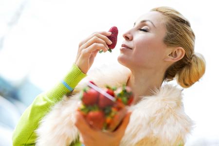 Kopen van de vrouw vruchten op de market.She onderzoekt een stukje van de producten. Stockfoto - 71299892