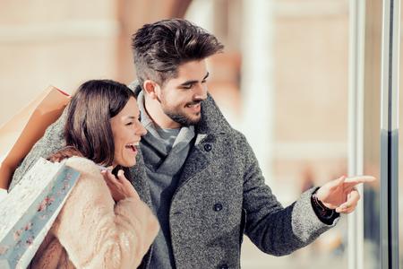 年輕夫婦抱著一個購物bags.Sale,消費主義和人的概念。