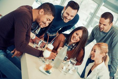 Amigos sonriendo y sentados en un café, beber café y disfrutando juntos.