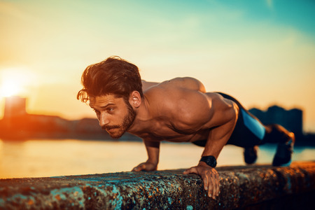 Portrait of a fitness man doing push ups outdoors. Stock Photo