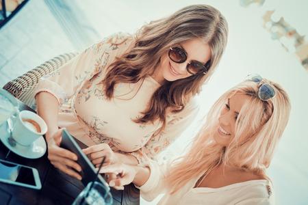 Amis ayant un grand moment dans cafe.Friends souriante et assis dans un café, boire du café et profiter ensemble. Banque d'images - 71325429