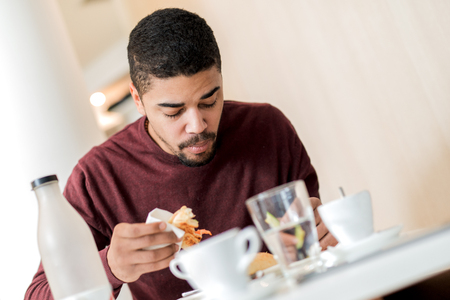 ハンサムなアフリカ系アメリカ人若者のカフェで朝食を持っています。