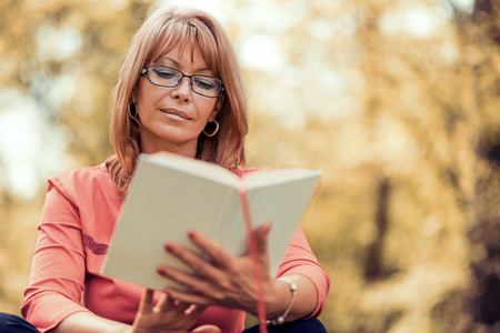 one mature woman only: Portrait of beautiful woman reading book in nature. Stock Photo