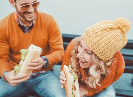 幸せな若いカップル。彼らは笑って、サンドイッチを食べて、楽しい時間を過ごしてします。 写真素材