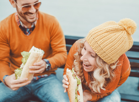 Happy young couple.They are laughing and eating sandwich and having a great time.