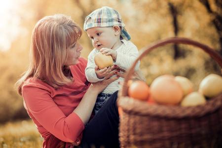 家庭在秋季park.Mom與兒子小時候玩在秋季性質。