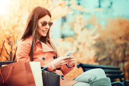 Retrato de una mujer sonriente bonita utilizar un teléfono móvil al aire libre Foto de archivo