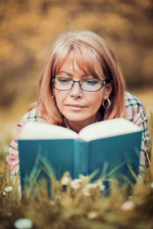 Portrait of beautiful woman reading book in nature. Stock Photo