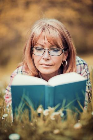 Portret van mooie vrouw leesboek in de natuur. Stockfoto - 71253851