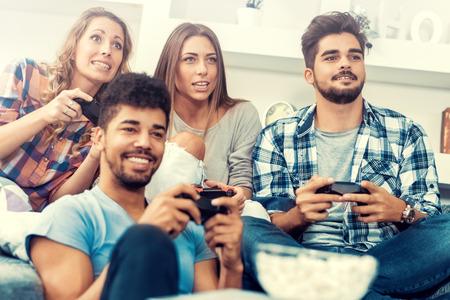 Jóvenes amigos jugando juegos de video en casa.