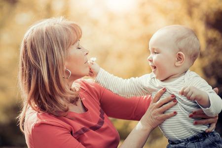 Madre feliz con su pequeño hijo en el parque de verano. Foto de archivo
