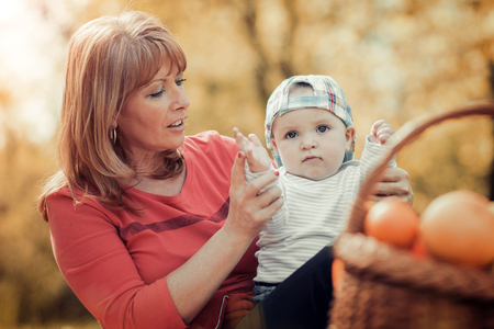 Family in the autumn park.Mom playing with son child in the autumn nature.