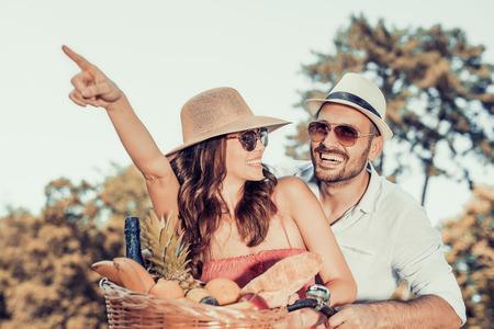 自転車のために行く幸せな若いカップルは公園で秋の日に乗る。 写真素材